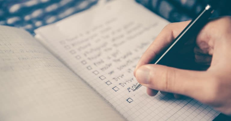 A person planning steps in a planner with a pen.