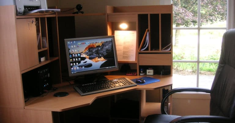 A decluttered corner desk in a home office.