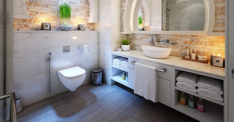 A bathroom with toilet, sink, counter, and space under the counter.