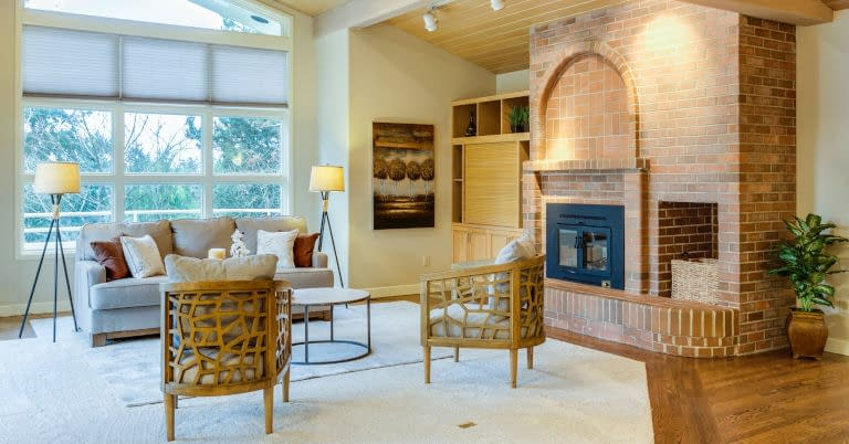 A decluttered living room with a brick fire place.