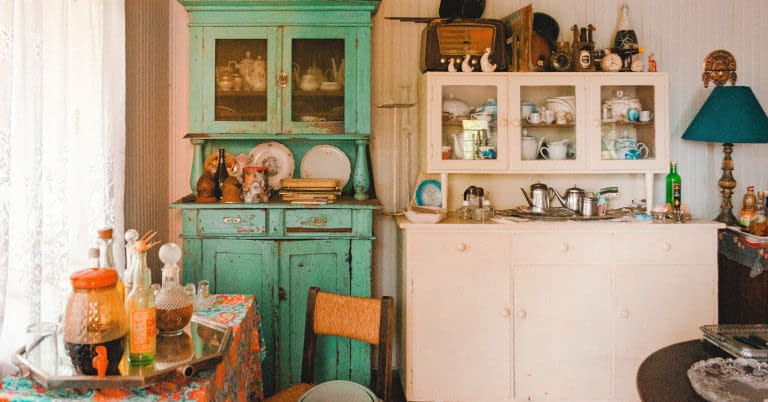 A kitchen with old furniture and items in and on cabinets and shelves.