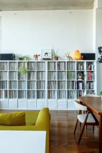 A decluttered living room with a couch, desk, and book shelves.
