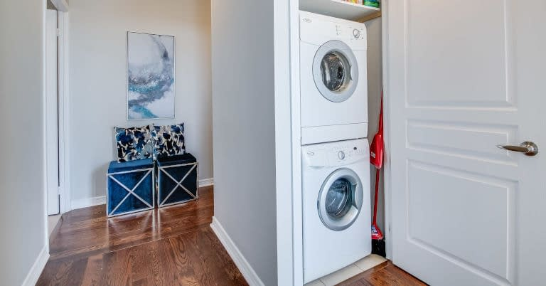 Decluttered laundry room with washer dryer closet.