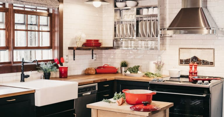 A decluttered kitchen sink, counter, and shelves.