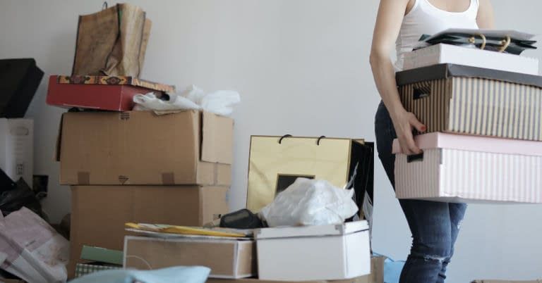 A woman decluttering by packing and moving boxes of clutter.