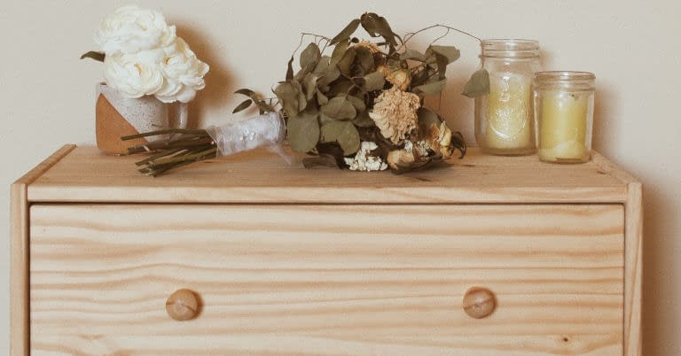 A clothes dresser drawer with flowers and candles.