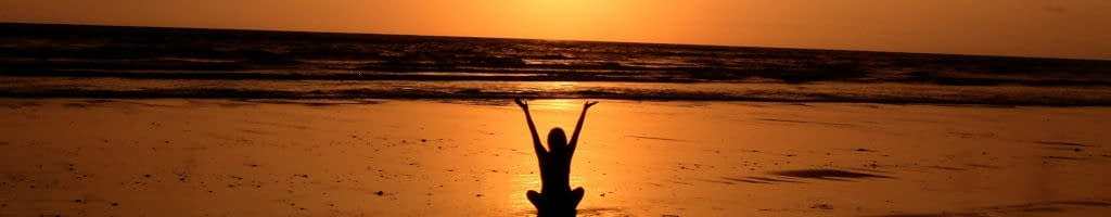 A peaceful woman on a beach at sunset.